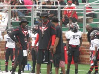 NFL Hall of Famer Deion Sanders, center, watches his Truth youth football team run a play against the Atlanta Cowboys.