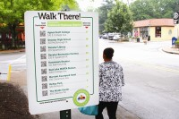 "A ""Walk There! Decatur"" sign in the Oakhurst business district shows local points of interest such as McKoy Park and The Wylde Center. Photos by Travis Hudgons"