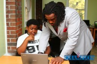 Babineaux shows 13-year-old Ahmone Talley how to turn on the laptop.