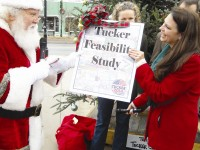 Santa Claus presents Tucker 2014 President Sonja Szubski the Tucker feasibility study, which said the Tucker community is financially feasible to form into a city.