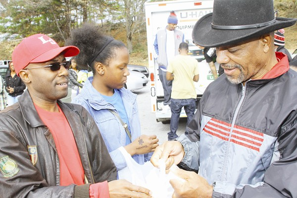 Left, Commissioner Larry Johnson lends a hand to pass out turkeys. Photos by Travis Hudgons