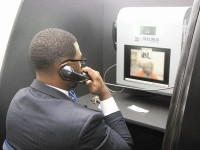 A Sheriff's Office employee uses the new system to talk with an inmate via a video phone. Photo by Andrew Cauthen