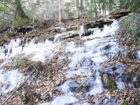 What is normally a small waterfall is frozen solid along the trail's edge.