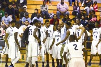 The Cedar Grove boys' basketball team huddle around head coach James Martin near the bench. Photo by Annette D. Ford