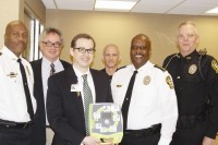 Eastside Medical Center Chief Financial Officer Jason Limbaugh, center, presented three automated external defibrillators to the Lithonia Police Department. Photos by Carla Parker