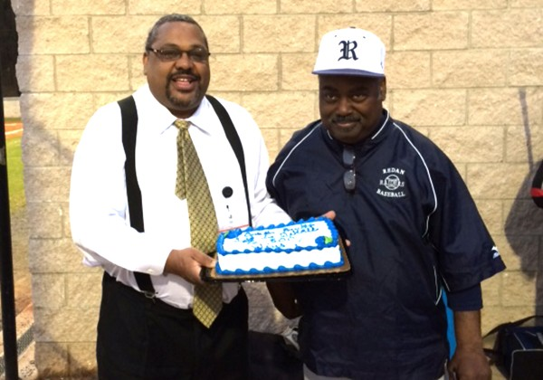 Redan High School principal Greg Goodwin (left) presents Redan baseball coach Marvin Pruitt with a cake in honor of his 500th career victory.