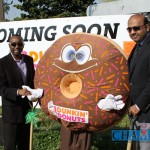 Commissioner Larry John, left, and owner Salman Badruddin stand with the Dunkin' Donuts mascot in front of the planned location of the Wesley Chapel Road Dunkin' Donuts slated to open this July. Photo by Travis Hudgons