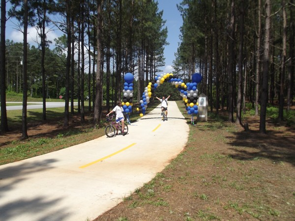 Jason Atkinson (left) of McDonough makes his way through an arch of balloons along the PATH in Conyers where a ribbon cutting was held to officially open the new section of the trail. Atkinson's daughter Cassidy waits for her dad to catch up. Photos by Gale Horton Gay