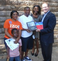 Eric Zeier of Bank of America in Atlanta presents a commemorative plaque to the Dukuly-Sasay family, which received its Habitat for Humanity DeKalb home in Stone Mountain.