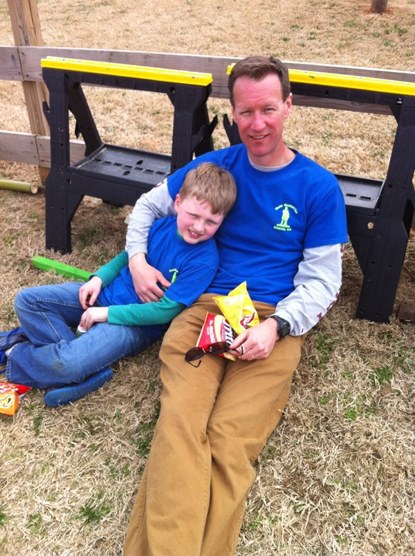 Matt Boettcher rests with his son Blake after a long day of Dads' Bucket List activities. Boettcher founded the group to lead fun activities with fathers and children.
