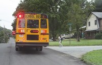 A student boards a school bus Aug. 11 on the first day of school for DeKalb County. Photo by Travis Hudgons