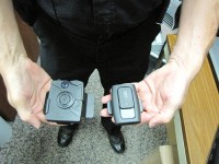 DeKalb County Police Officer Michael Freeman displays two of the body cameras the department is testing. Photo illustration by Andrew Cauthen