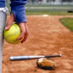 A girl holds a softball on the infield diamond.