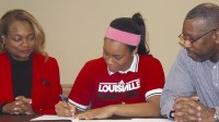 St. Pius guard Asia Durr (center) signs here letter of intent to Louisville as her parents look on. Left, Asia Durr celebrated her signing with family and teammates. Photos by Carla Parker