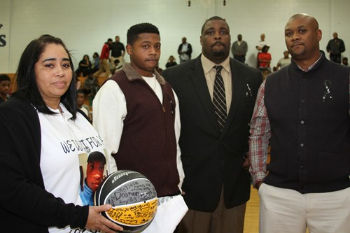 Monique Love and Cameron Love, wife and son of Coach Dannie Love, received a signed basketball from girls' basketball coach Jerry Jackson and boys' assistant basketball coach Cornell Cullom.