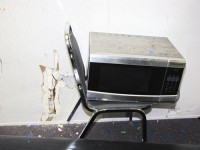 Recruits take breaks in a dilapidated building. Their microwaves sits precariously on a chair in front of a wall with a hole. Photos by Andrew Cauthen
