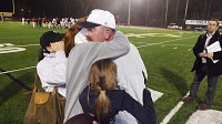 St.Pius X head coach Paul Standard is embraced by his family after the Golden Lions knocked off Woodward Academy to advance to the state championship. Photo by Carla Parker