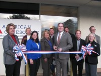 Surrounded by health center staff, DeKalb Chamber of Commerce staff and other well-wishers, Dr. Frank Lockwood cuts the ribbon to officially open the new facility.