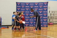 Coaching staff for the Atlanta Hawks basketball team instructs children through drills.