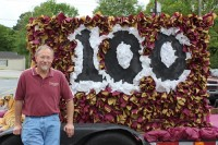 Former German teacher Bob McCormick poses in front of the Tucker centennial float.