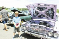 Youngster Skylar stands next to a renovated vehicle in the Doraville car show.