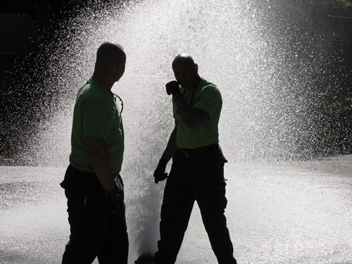 Two fire department recruits hold down a fire hose during a hydrant test. Photos by Andrew Cauthen