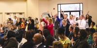 A group attending the DeKalb County Board of Commissioners' meeting raise their hands to announce their support of the rezoning of LaVista Office Park to redevelop a retail shopping center. Photo by Travis Hudgons