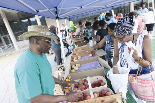 Residents receive free fresh produce during an event celebrating the launch of the county's mobile farmers market. Photo by Travis Hudgons