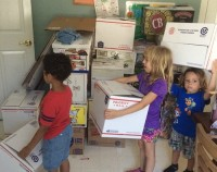 Youngsters assist in packing up their school's supplies.