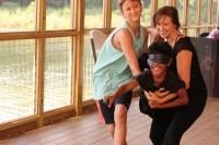 "Camper Zayden Trotter is cradled by fellow camper and camp counselor Sara Gregory in the ""Shine On"" performance."