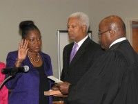 From left, DeKalb Commissioner Mereda Davis Johnson takes the oath of office as her husband, Congressman Hank Johnson, looks on. Superior Court Judge Gregory Adams administered the oath.