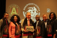DeKalb County commissioners present Arthur Blank with a plaque in recognition and appreciation for bringing professional soccer to DeKalb County.
