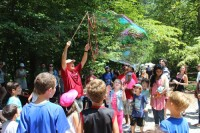 Festival volunteer uses two strings and bucket of soap to entertain dozens of youngsters by creating giant bubbles.