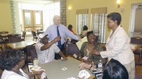 Bettye Davis, right, and program coordinator Henry Rosenthal chat with members of the Lou Walker Senior Center.