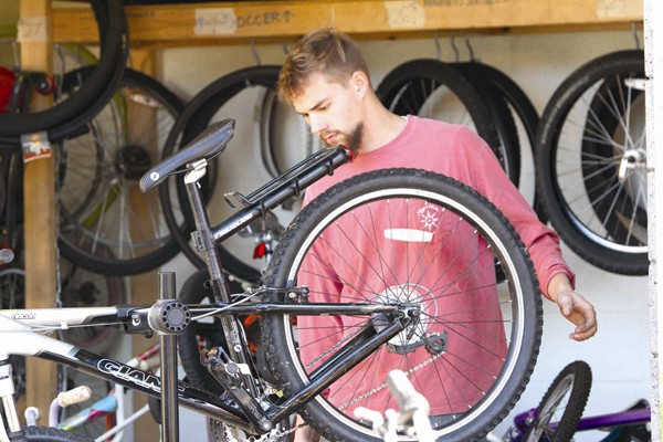 Communicycle employees and volunteers assist residents in repairing their bicycles and sell bikes for less than $35.
