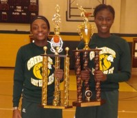 From left, Arielle Holloway and Theodora Odia hold the holiday tournament trophies Greenforest won in December.