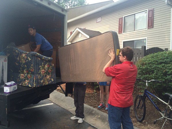 New American Pathway volunteers unload a truck of furniture for refugees' apartments.