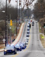 A long line of law enforcement vehicles travels along Memorial Drive for the funeral of a Riverdale police major. Photos by Andrew Cauthen