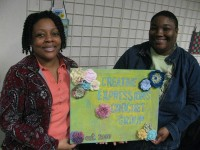 Shantrice Whitehead, left, and Tamika Strong show a sign for the organization they helped to found. Photos by Kathy Mitchell