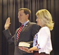 Frank Auman is sworn in as his wife Gaye looks on.