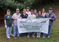 Volunteers from Paran Homes, Smith Douglas Homes, Greater Atlanta Home Builders Association and other organizations display a sign that summarizes their commitment to projects to help the homeless.