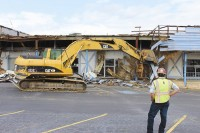 A bulldozer begins reducing Lithonia Plaza to rubble. In approximately 45 days, this eyesore in Lithonia will be no more. Photos by Andrew Cauthen