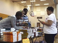 Eighth-graders Jakeria Daniels, Tyrees Lindsey and Deshawn Williams help an educator select books at Bethune Middle School.