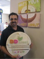 Owner Barkat Colabawala shows the plaque that tells customers his store meets Dunkin' Donuts' DD Green environmental standards.