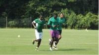 Members of the Nigerian Olympic soccer team jog around the field during warm-up.