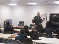 Retired DeKalb County captain Roderick Morgan talks to a group of local youth about bullying and law enforcement as part of the DeKalb County Sheriff's Office Junior Deputy summer camp. East precinct Education Specialist Emmitt Jenkins said community programs help combat crime in the area. Photo by Horace Holloman