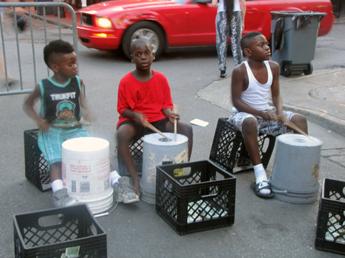 Three young street performers play on makeshift drums for cash on Bourbon Street
