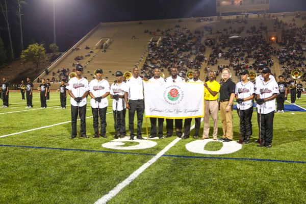 MLK High band director Travis Kimber along with his assistants and drum majors are presented with the Tournament of Roses Parade Flag from the President of the Tournament of Roses Parade Brad Ratliff, during halftime Aug. 27 at Hallford Stadium.