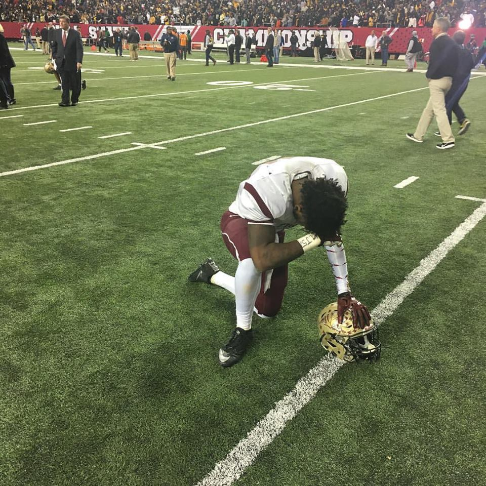A Tucker player kneels in dejection after Tucker lost to Valdosta in the Class 6A title game. Photo by Carla Parker