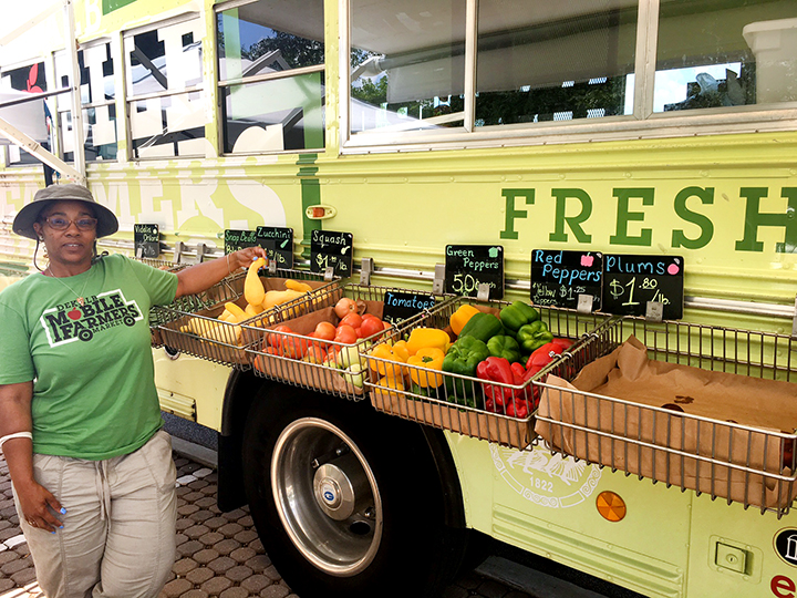 Joelette Bembry of the DeKalb Extension Service shows fresh peppers that were for sale when the Mobile Farmers Market stopped June 8 at the Scott Candler library branch.